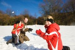 Vader met jonge geitjes die een sneeuwbalstrijd in de winter hebben Stock Foto's