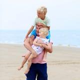 Vader met jonge geitjes die pret op het strand hebben Royalty-vrije Stock Afbeeldingen