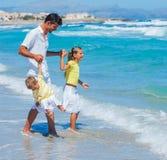 Vader met jonge geitjes op strand stock afbeeldingen