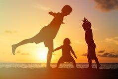 Vader met jonge geitjessilhouetten die pret hebben bij zonsondergang Royalty-vrije Stock Foto's