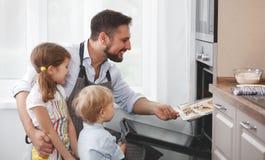 Vader met kinderen die koekjes bakken Stock Foto