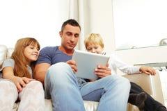 Vader met kinderen die op tabletcomputer spelen Royalty-vrije Stock Afbeeldingen