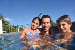 Vader met kinderen die pret in zwembad hebben royalty-vrije stock foto