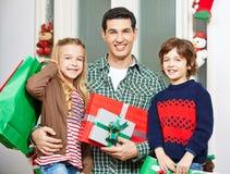 Vader met kinderen en giften bij Kerstmis Royalty-vrije Stock Afbeeldingen