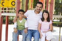 Vader met kinderen in speelplaats Stock Foto's