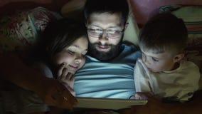 Vader met kleine kinderen die op tabletcomputer vóór slaap surfen stock videobeelden
