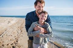 Vader met kleine zoon op een gang in openlucht op strand, die pret hebben stock foto