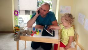 Vader met mobiele telefoon spreken en zijn kind die met tabletcomputer spelen stock video