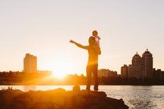 Vader met weinig kind bij zonsondergang Stock Afbeeldingen