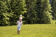 Vader met weinig zoon die op schouders op een groene weide op een achtergrond van groene pijnboombossen lopen stock afbeelding