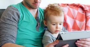 Vader met zijn babyjongen die digitale tablet in woonkamer 4k gebruiken stock footage