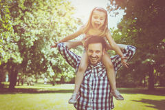 Vader met zijn dochter in weide Meisjezitting o Royalty-vrije Stock Foto