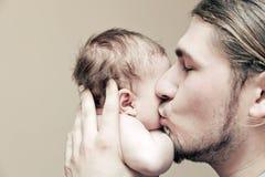Vader met zijn jonge baby die en hem knuffelen kussen op wang Royalty-vrije Stock Foto's