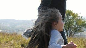 Vader met zijn twee dochters met een luchtballons die van de heuvel leeglopen stock video
