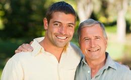 Vader met zijn zoon die de camera bekijkt Stock Afbeelding