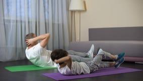 Vader met zoon die buikkraken doen die thuis, voordeel van sporten tonen stock footage