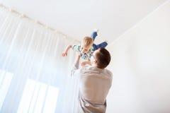Vader met zoon die en pret thuis spelen hebben Royalty-vrije Stock Afbeeldingen