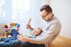 Vader met zoon die en pret thuis spelen hebben Stock Foto's