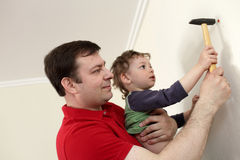 Vader met zoon die plastic anker hameren Stock Foto