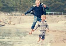 Vader met zoon het lopen op de overzeese brandingslijn Royalty-vrije Stock Afbeelding