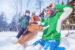 Vader met zoon het spelen met hun hond in diepe sneeuw Stock Foto