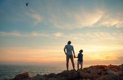 Vader met zoon op de overzeese kust in zonsondergangtijd Stock Foto