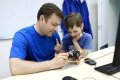 Vader met zoon programmeringsrobot Stock Afbeeldingen