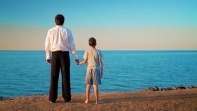 Vader met zoonstribune door de hand door het overzees stock videobeelden
