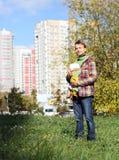 Vader met zuigelingsbaby in slinger, de volledige groei Royalty-vrije Stock Fotografie