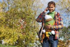 Vader met zuigelingsbaby in slinger die op een celtelefoon spreken Stock Afbeeldingen