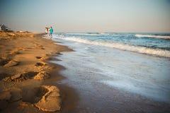 Vader, moeder en jonge geitjes die langs het strand lopen Nadruk op voetstappen in het zand Royalty-vrije Stock Afbeelding