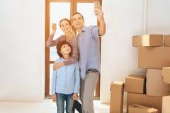Vader, moeder en zoon in nieuwe flat met kartondozen De familie neemt selfie op telefoon stock foto's
