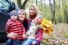 Vader, moeder, zoon en dochter met esdoornbladeren stock afbeelding