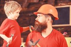 Vader, ouder die met baard in beschermende helm weinig zoon onderwijzen om verschillende hulpmiddelen in schoolworkshop te gebrui stock fotografie