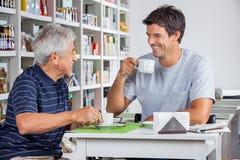 Vader And Son Communicating terwijl het Hebben van Koffie stock afbeeldingen