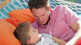 Vader And Son Relaxing in Tuinhangmat samen stock videobeelden