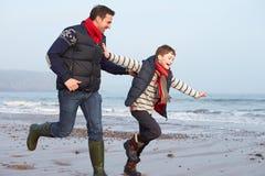 Vader And Son Running op de Winterstrand Stock Fotografie