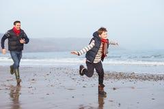 Vader And Son Running op de Winterstrand royalty-vrije stock afbeelding