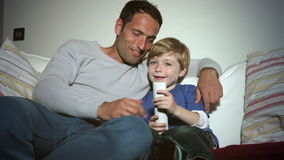 Vader And Son Sitting op Sofa Watching-TV samen stock video