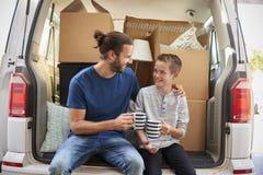 Vader And Son Take een Onderbreking in Rug van Verwijdering Van On Moving Day royalty-vrije stock foto