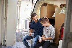 Vader And Son Take een Onderbreking in Rug van Verwijdering Van On Moving Day royalty-vrije stock foto's