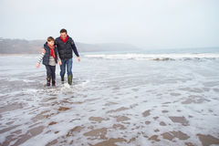 Vader And Son Walking op de Winterstrand royalty-vrije stock afbeeldingen