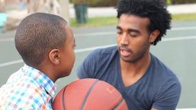 Vader Teaching Son How om Basketbal te werpen stock footage