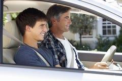 Vader Teaching Teenage Son om te drijven royalty-vrije stock afbeeldingen