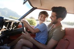 Vader Teaching Young Son om Auto op Wegreis te drijven stock fotografie