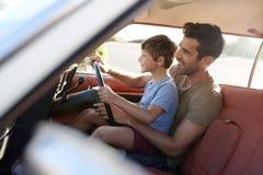 Vader Teaching Young Son om Auto op Wegreis te drijven royalty-vrije stock foto