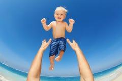 Vader trowing omhoog hoog in de lucht een gelukkig kind Stock Afbeeldingen