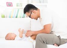 Vader veranderende luier en kleren voor baby Royalty-vrije Stock Foto