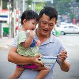 Vader voedende dochter op de straat van Ho Chi Minh, Vietnam Royalty-vrije Stock Fotografie