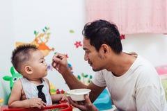 Vader waarnemend Mamma die zijn zoonsbaby 1 éénjarige op stoel voeden stock fotografie